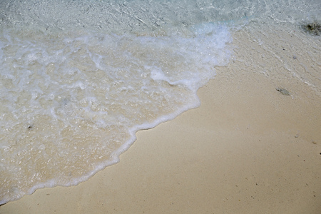 Blue ripples waving towards sea sand beach shore from top view for summer and vacation background