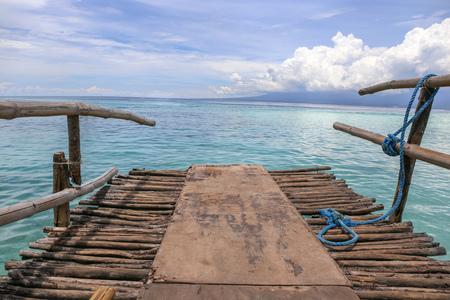 Wood dock pier on beautiful ocean sea water in seashore scene background with wide perspective
