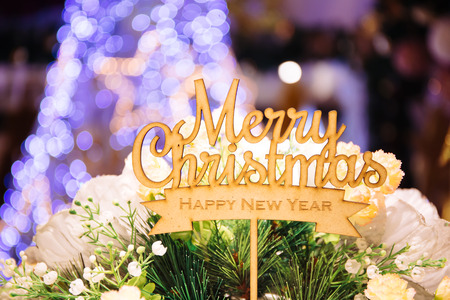 Merry Christmas and happy new year text sign topper stick on the top of bouquets with xmas tree in the background bokeh