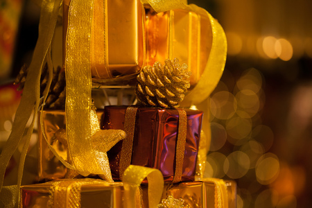 Close-up of golden gifts piled up in stack blurred in gold bokeh background - (selective focus) Stok Fotoğraf