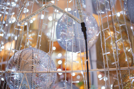 Close-up of beautiful decorated Christmas tree in shape of light trail with silver baubles inside Stock Photo