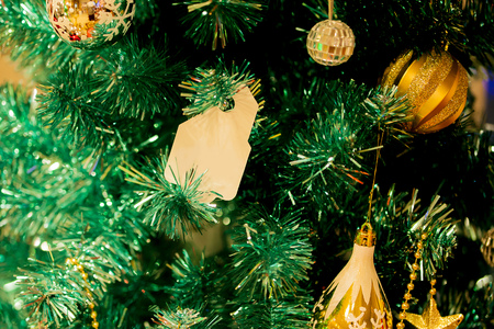 Christmas tree decorated with beautiful golden ornaments and empty card hanging - to insert any text Stock Photo