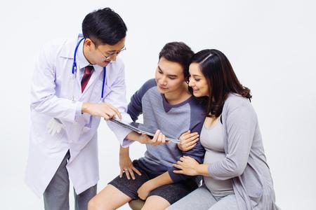 妊娠中の女性と夫のカップルに婦人科医または産科医医師の示す超音波写真 写真素材
