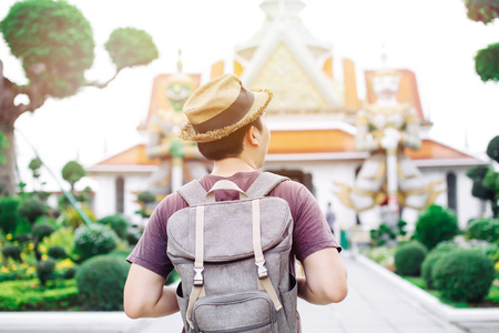 Young Asian traveling backpacker in Wat Arun in Bangkok, Thailand