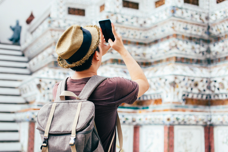 Young Asian traveling backpacker taking photos with smartphone in Wat Arun in Bangkok, Thailand Stock Photo