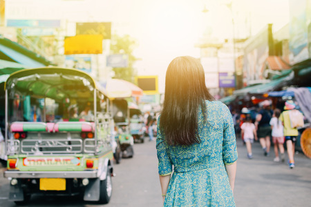 Woman in traditional Asian dress on Khaosan road with tuk tuk taxi behind, appreciating Thai local culture - travel and local life concept