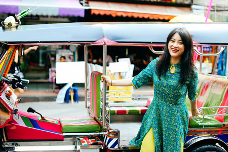 Woman in traditional Asian dress posing for photo while getting off tuk tuk, Thai traditional three wheel taxi in Bangkok, Thailand