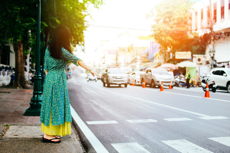 Woman in traditional Asian dress standing on the pathway waving for transportation service such as taxi or bus in Bangkok, Thailand
