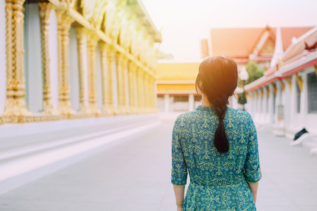 Woman in traditional Asian dress walking inside the temple in Bangkok, Thailand, appreciating Buddhism and Thai culture
