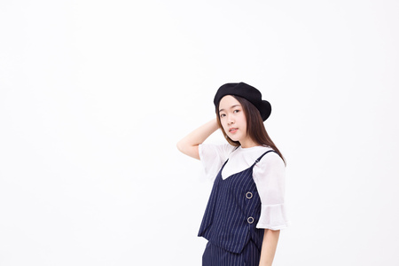 Young and pretty Asian female with artist hat smiling and posing in white isolated background