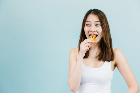 Asian woman with mouth opened eating eat deep fried chicken legs drumstick