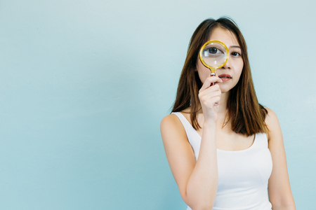 Young Asian woman with magnifying glass isolated on a blue pastel background