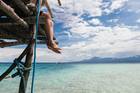 Young man relaxing and sitting on edge of sea beach pier in summer beach scenery