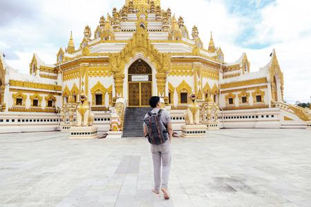 ミャンマー・ヤンゴンの仏遺物歯パゴダというビルマ寺院に向かって歩く若者のバックパッカーの背中 写真素材