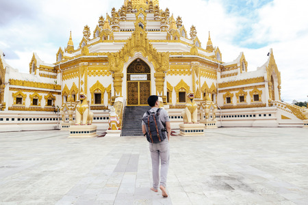Back of young man backpacker walking towards Burmese temple named Buddha  Relic Tooth Pagoda in Yangon, Myanmar