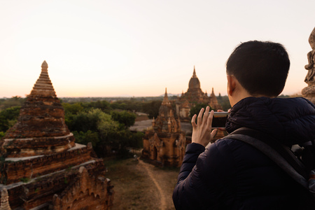 Young man taking a photo with mobile phone in temple stupa scene behind in Bagan, Myanmar