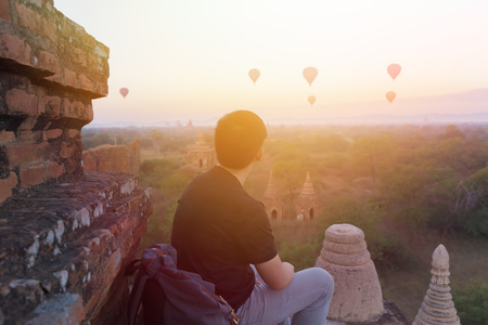 Silhouette of young male backpacker sitting and watching hot air balloon travel destinations in Bagan, Myanmar Stock Photo