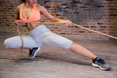 Young attractive athlete muscular woman in sportswear exercising crossfit workout with rope over red brick background