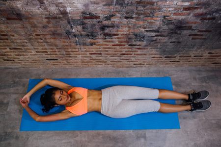 Young sporty muscular woman lying on exercise mat performing sit-ups. Top view of woman in sport clothing doing abs crunches in vintage gym
