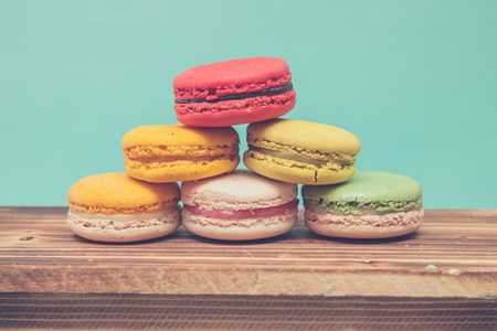 Pile of colorful macarons stacked up like a tower in blue turquoise pastel isolated background on wood table Stock Photo