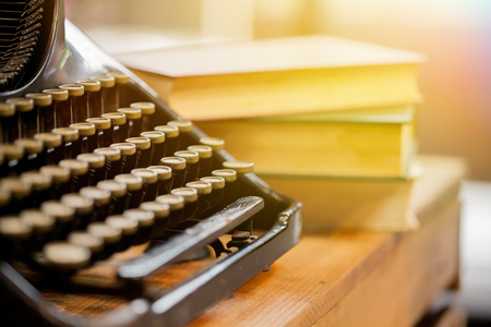 Old and vintage type writer machine and piles of books on wooden table - very selective focus Stok Fotoğraf