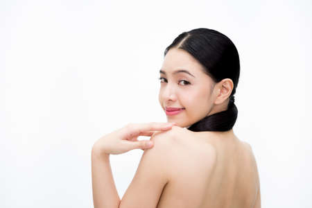 Young beauty Asian woman turning smiling face and showing bare back isolated over white background. Healthcare and Skincare concept