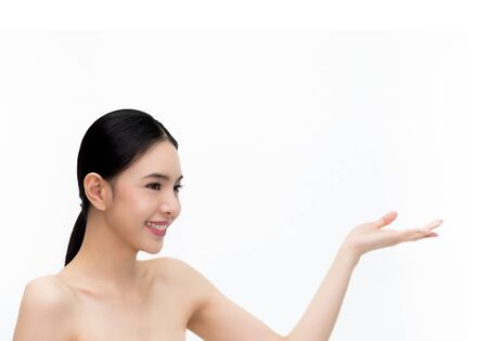Young beauty Asian face, beautiful woman showing empty hand isolated over white background. Healthcare and Skincare concept Stock Photo