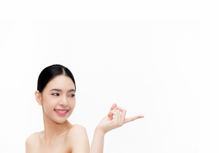 Young beauty Asian woman pointing finger on empty white copy space isolated over white background. Healthcare and Skincare concept with space for marketing and advertising