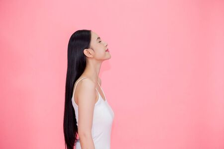 Side view of Young beautiful and calm Asian woman isolated over pink background Stock Photo