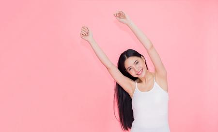 Gelukkige en vrolijke glimlachende Aziatische jaren '20vrouw die handen omhoog voor positief die gevoel en viering opheffen over roze achtergrond wordt geïsoleerd Stockfoto - 96380898