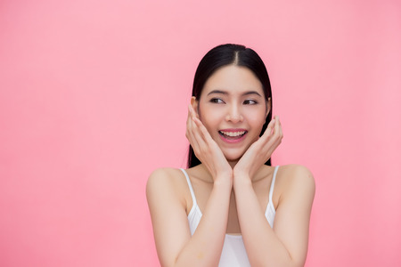 Excited and surprised smiling Asian 20s woman isolated over pink background