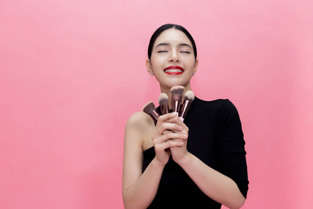Young Stylish Asian woman carrying makeup brushes on hand with copy space. Beautiful fashionable woman isolated over pink background