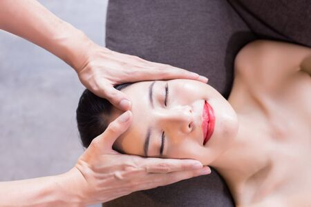 Young attractive and relaxing Asian 20s woman being massaged by massage therapist at home Stock Photo