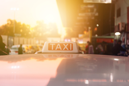 Taxi sign on the roof of taxi cab on the busy street over yellow orange warming sunset background Foto de archivo - 96710522