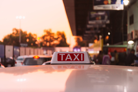 Taxi sign on the roof of taxi cab on the busy street over yellow orange warming sunset background Stock Photo
