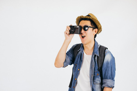 Young Asian tourist with hat and sunglasses smiling and holding camera isolated over white background Stock Photo