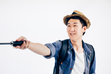 Young Asian tourist with hat smiling and holding selfie stick taking a selfie photo isolated over white background Stock Photo