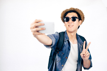 Young Asian tourist with hat smiling and holding smartphone taking a selfie photo isolated over white background