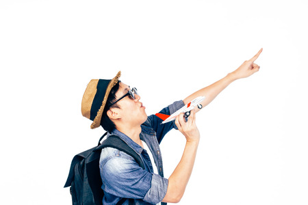 Ambitious young tourist pointing up to the sky dreaming to travel isolated over white background - Travel and Backpack Ambition concept