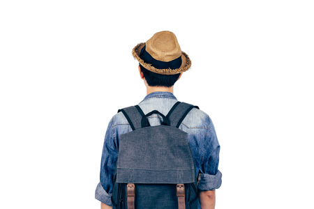 Back of young tourist with hat standing over white background. Backpackers looking the view isolated