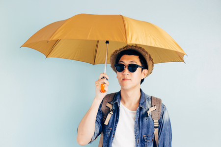 Young Asian tourist holding umbrella isolated over pastel blue background. Alone and Looking for partner to travel Stock Photo