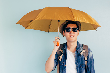 Young Asian tourist smiling and holding umbrella isolated over pastel blue background. Alone and Looking for partner to travel Banco de Imagens