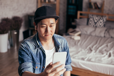 Young Asian man expressing serious look while talking video call via smartphone wearing headphones at home