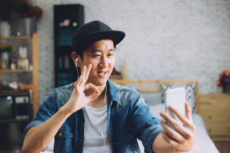Unterhaltungsvideoanruf des jungen glücklichen asiatischen Mannes über tragende Kopfhörer des Smartphone zu Hause Standard-Bild