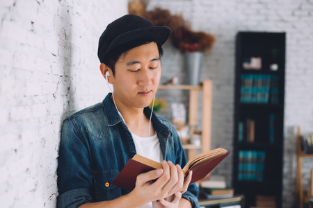 Young Asian man reading book in living cozy room