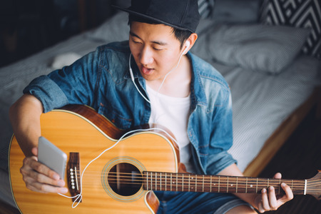 Young Asian man using a mobile phone with headphones while playing guitar in cozy bedroom Stock Photo