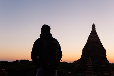 Silhouette of young travel man watching sunrise in temple pagoda area Stock Photo
