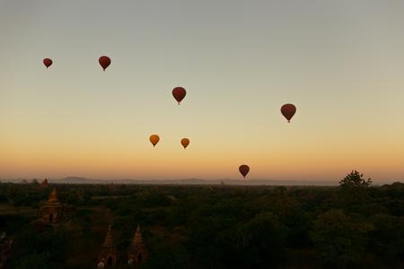 Hot air balloons floating around Burmese pagoda heritage site during sunrise landscape Stock Photo