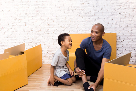 African American parent with child smiling and packing stuff for moving in to the new house.