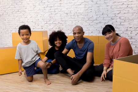 African American parents with children smiling and packing stuff for moving in to the new house Stock Photo